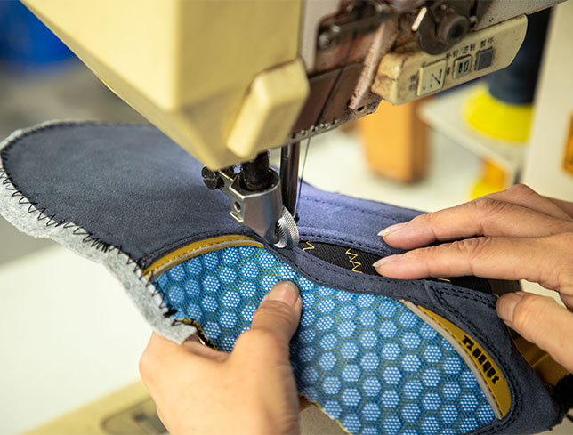 Worker using a sewing machine to combine components of a safety shoe together