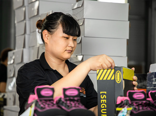 Woman worker carefully packing safety shoe products